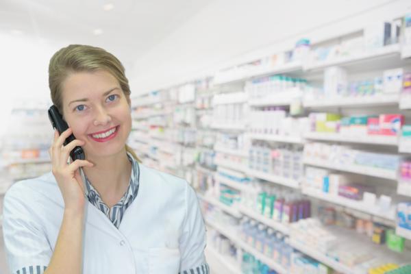 Une spécialiste parle au téléphone devant un rayon de médicaments